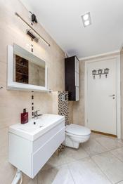 Baderommet er innredet med dusjhjørne med glassdører og håndholdt dusjarmatur, vegghengt toalett, speilskap og vask med underskap.
