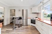 Kjøkkeninnredning med hvite profilerte fronter og laminerte benkeplater.