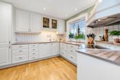 Hvit Mias kjøkkeninnredning fra 2007 med fliser over laminat kjøkkenbenk.