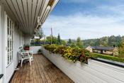 Vestvendt balkong hvor det er montert markise og pene blomsterkasser.