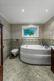 Badet har boblebadekar, vegghengt toalett og dusjhjørne innsvingbare dører.