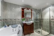 Det er montert downlights i taket og baderomsinnredning med servant og tilhørende overskap med speil.