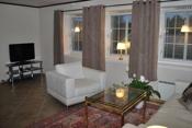 Stue med flislagt gulv og lyse overflater. Vinduer som gir mye lys til rommet.