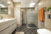 I tilknytning til de to gode soverommene er det et delikat flislagt bad/vaskerom