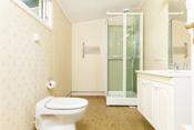 Bad med servantskap, vakuum toalett og dusjkabinett.