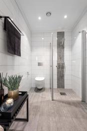 Badet i 1.etasje har baderomsinnredning, speil med integrert belysning, dusjnisje og veggfestet wc.