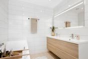 Boligen har 2 moderne bad. Badet i underetasjen har lekker baderomsinnredning med dobbel servant og underskuffer, stort speil med integrert belysning.