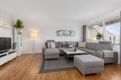 Romslig stue med god plass til en sofakrok, tv, og diverse møbler.