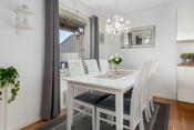 Fin plass til spisebord og stoler som gir en hyggelig sone på kjøkkenet.