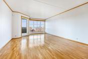 Romslig stue med store vindusflater som gir rommet rikelig med naturlig lys.