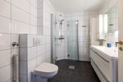 Nyere flislagt baderom - Vegghengt wc, dusjhjørne med glassvegger, pen baderomsinnredning og opplegg for vaskemaskin.