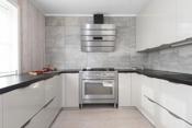 Stor gasskomfyr med elektrisk stekeovn fra Ariston. Integrert oppvaskmaskin og kjøleskap.