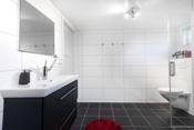 Badet inneholder veggmontert klosett, dusjnisje med nisjefront i glass og servantskap med hel servantplate.