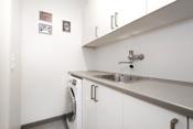 Praktisk separat vaskerom med flislagt gulv. Pen og praktisk innredning med utslagskum.