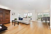 Stor luftig stue med åpen løsning mot kjøkken.