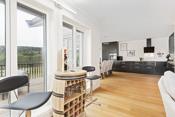 Store vindusflater som gir stuen og kjøkkenet rikelig med naturlig lys. Det er montert elektrisk solskjerming mot syd.