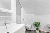 Rommet er innredet med baderomsinnredning med lyse fronter og overhengende speilskap. Dusjen er plassert i egen nisje og har dusjoppheng, dusjarmaturet er håndholdt.