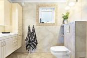 Pent, flislagt bad som er innredet med vegghengt toalett, dusjnisje med buede glassvegger og dusjgarnityr og blandebatteri på vegg.