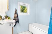 Badet er innredet med fliser på gulv og våtromsplater/ respatex på vegger. Rommet er innredet med baderomsinnredning på 90 cm med underskap med heldekkende servantplate, overskap og speil med lys. Badekar. Varmekabler.