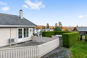 Det er usjenerte uteplasser med terrasse, hellelagt plass med tujahekk rundt og plen foran bolig med tujahekk rundt.