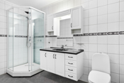 Bad har varmekabler og fliser på gulv, fliser vegger og malt tak. Rommet er innredet med dusjkabinett, gulvmontert toalett, baderomsinnredning på 1,2 meter med underskap med skap og skuffer, heldekkende plate med servant, overskap med speil og lys.