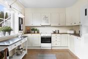 Kjøkken med åpen løsning mot spisestuen. Innredning i L-form med profilerte lyse fronter.