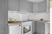Kjøkkeninnredningen har malte profilerte fronter, benkeplate i laminat med nedsenket oppvaskkum. Flisplater mellom over og underskap. Plass for komfyr med ventilator over, plass og opplegg til oppvaskmaskin