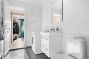 Rommet er innredet med dusjkabinett, gulvmontert toalett, 60 cm baderomsinnredning med skuffer og heldekkende servant, speil med lys over. Plass og opplegg til vaskemaskin