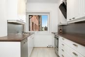 Kjøkkeninnredning med hvitmalte profilerte fronter, laminerte benkeplater med beslag med oppvaskkum. Fronter på innredning er ifølge eier malt opp 2011 samtidig ble også benkeplater skiftet.