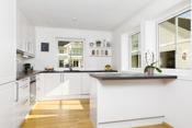 Meget godt kjøkken med integrerte hvitevarer og innredning i hvit profilert utførelse samt barløsning