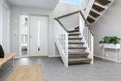 Lys og romslig hall med plass for garderobe, fliser på gulvet og varmekabeler til oppvarming
