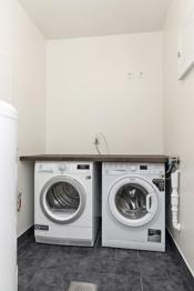 Bod/vaskerom med opplegg for vaskemaskin, fliser på gulvet og sluk i gulvet