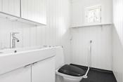 Våtromsbelegg med oppbrett på vegg. Smartpanel på vegger. Rommet er innredet med gulvmontert toalett, baderomsinnredning på 80 cm med heldekkende servant med skap under og speilskap med lys over.