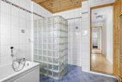 Det er gulvmontert toalett, badekar og dusjnisje med glassbyggestein.