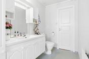 Bad med gulvbelegg med oppbrett på vegg, våtromstapet på vegger og takess i tak.