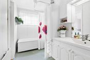 Rommet er innredet med badekar med blandebatteri, dusj med forheng, med blandebatteri og dusjgarnityr på vegg.