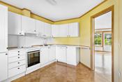 Kjøkken med plass til spisegruppe. Innredningen er fra byggeåret, og har profilerte, lyse fronter og laminerte benkeplater.