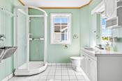 Bad/vaskerom med flislagte overflater på gulvet samt sokkelflis og våtromstapet på vegger.