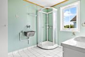 Dusjkabinett med dører av glass, dusjarmaturet er håndholdt. Det er opplegg og plass til vaskemaskin i rommet. Utslagsvask av rustfritt stål er montert på veggen.