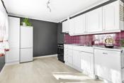 Kjøkken med hvite profilerte fronter, laminert benkeplate med nedsenket oppvaskbeslag med 2 stk oppvaskkummer.