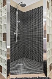 Badet er innredet med vegghengt toalett, dusjnisje med vegger i glassbyggerstein, dusj med fast dusjhode og dusjgarnityr