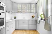 Det er flisplater mellom over og underskap. Det er innbygde hvitevarer med oppvaskmaskin, kjøleskap og frys, komfyr og Micro. Det er nedfelt komfyrtopp med ventilator over