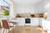 Kjøkken med åpen løsning mot stuen. Innredning i L-form med lyse profilerte fronter.