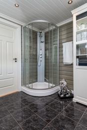 Badet har flislagt gulv med varmekabel og trepanel på vegger.