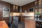 Kjøkkeninnredning med integrert kjøl og frys, komfyr, platetopp, oppvaskmaskin, ventilator, micro og kaffemaskin.