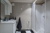 Badet i kjeller er innredet med dusjkabinett, veggtoalett, innredning med servant og opplegg til vaskemaskin