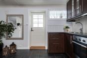 Kjøkkenkrok i kjeller med integrert komfyr, platetopp og ventilator
