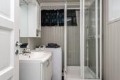 Bad i kjeller med dusjkabinett, veggtoalett, innredning med servant og opplegg til vaskemaskin.