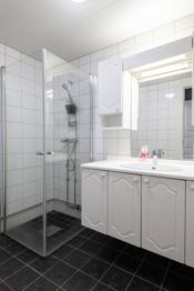 Badet er innredet med dusjhjørne og innredning med servant.