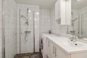 Badet har varmekabler, dusjhjørn med innfellbare dører, toalett, innredning og opplegg til vaskemaskin